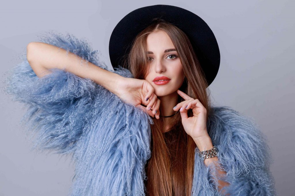 close up indoor fashion portrait pretty young model stylish winter fluffy coat black hat posing evening bright make up